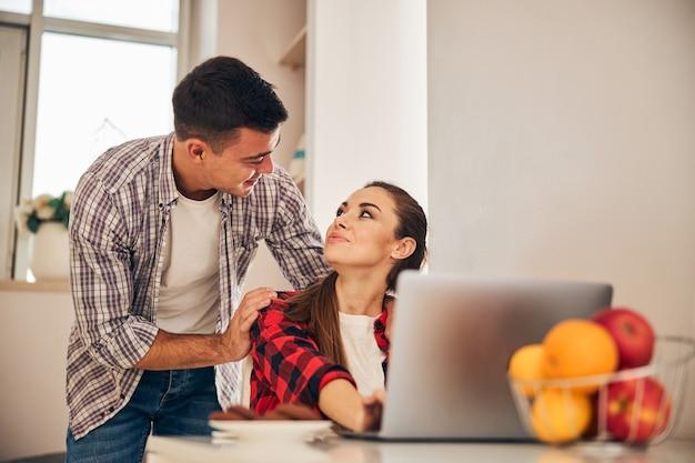 Weiblicher telearbeiter, der ihren hübschen männlichen ehepartner betrachtet
