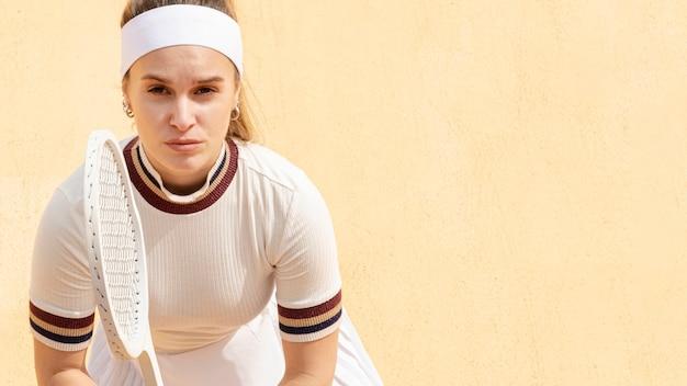 Weiblicher tennisspieler der nahaufnahme vorbereitet, den ball zu schlagen