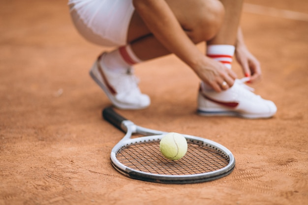 Weiblicher tennisspieler, der sich oben die schuhe, füße schnürt