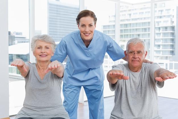 Weiblicher therapeut, der ältere paare mit übungen unterstützt