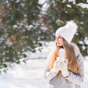 Weiblicher tierarzt, der mitnehmer kaffeetasse hält, die im winter steht