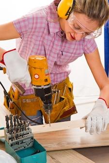 Weiblicher tischler bei der arbeit unter verwendung der handbohrmaschine