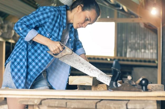 Weiblicher tischler mit der metallsäge, die bretter in der werkstatt sägend