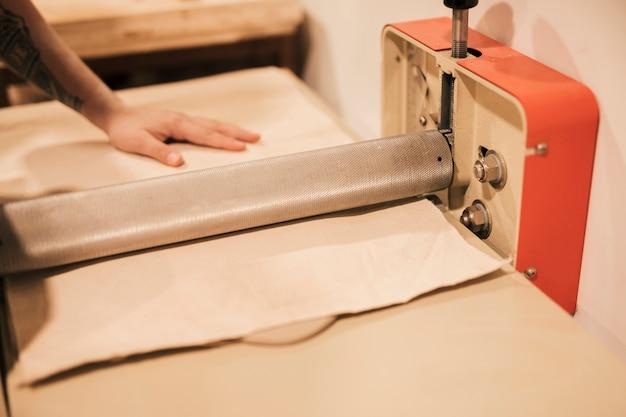 Weiblicher töpfer, der den lehm unter dem papier mit maschine flach macht
