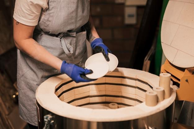 Weiblicher töpfer, der den prozess des trocknens von keramikplatten vereinbart