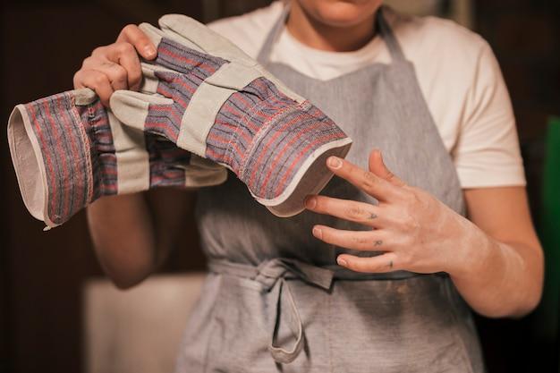 Weiblicher töpfer, der die handhandschuhe entfernt