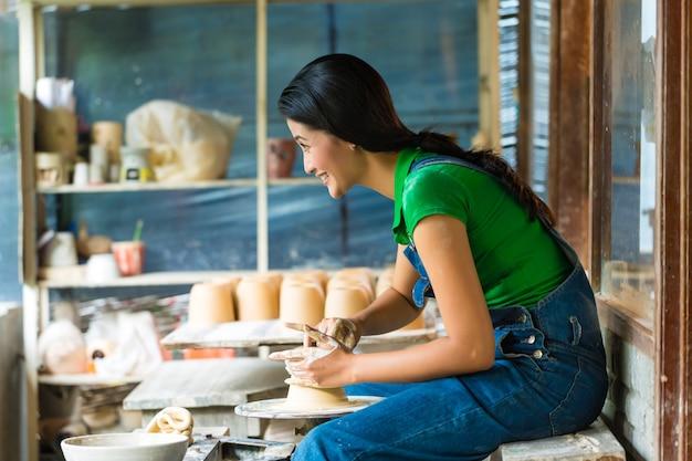 Weiblicher töpfer, der eine schüssel auf einem töpferscheiben herstellt