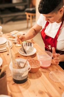 Weiblicher töpfer, der keramischen dishware mit malerpinsel in der werkstatt malt