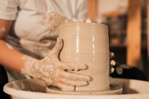 Weiblicher töpfer, der topf in der tonwarenwerkstatt formt