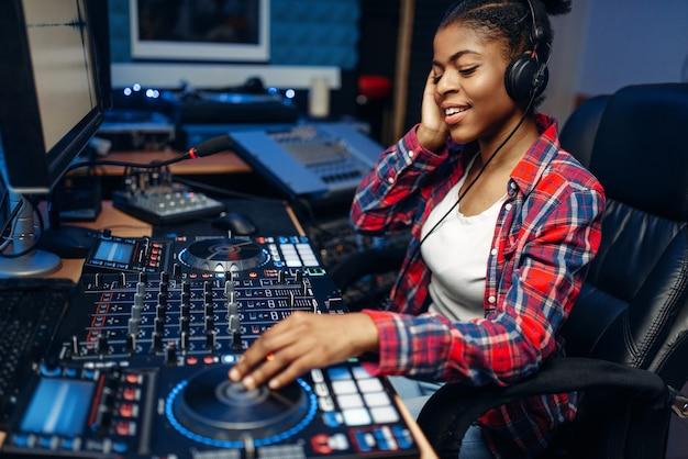Weiblicher tonbediener, der an der fernbedienung im audioaufnahmestudio arbeitet. musiker am mixer, professionelles musikmischen