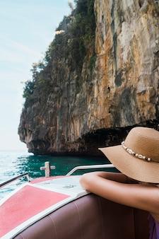 Weiblicher tourist, der auf bootsreise nahe der klippe sich lehnt