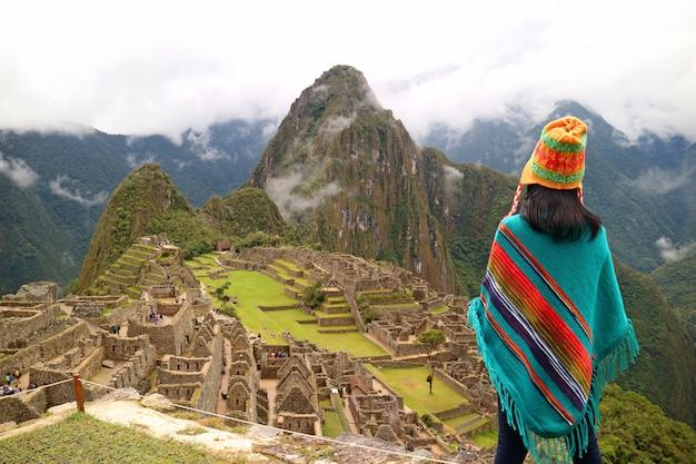 Weiblicher tourist, der die berühmten alten inkaruinen von machu picchu, cusco-region, peru betrachtet