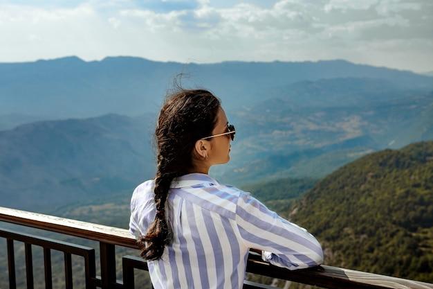 Weiblicher tourist, der die schöne ansicht der berge betrachtet