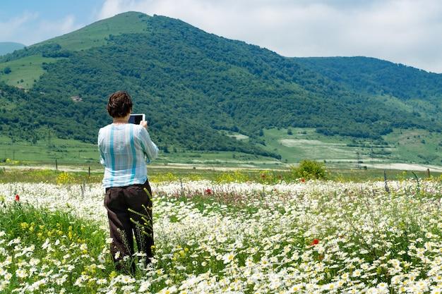 Weiblicher tourist, der fotos mit digitalem tablett macht, das im schönen feld voller blühender blumen vor den bergen in armenien steht
