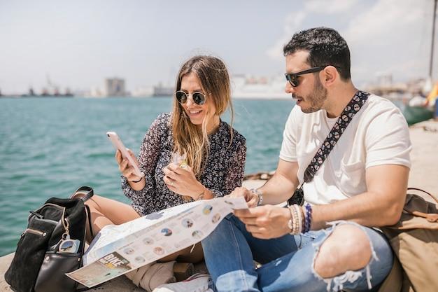 Weiblicher tourist, der ihren freundhandy sitzt auf anlegestelle zeigt