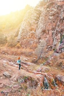 Weiblicher tourist, der im bergwald geht tourist mit einem rucksack steht in einer bergschlucht bei sonnenuntergang herbstwanderung in den bergen eine rothaarige junge frau mit einem blauen rucksack
