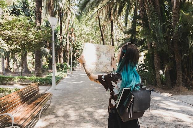 Weiblicher tourist, der karte im park betrachtet