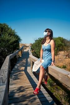 Weiblicher tourist in einer wegwerfmaske, die auf der brücke sitzt