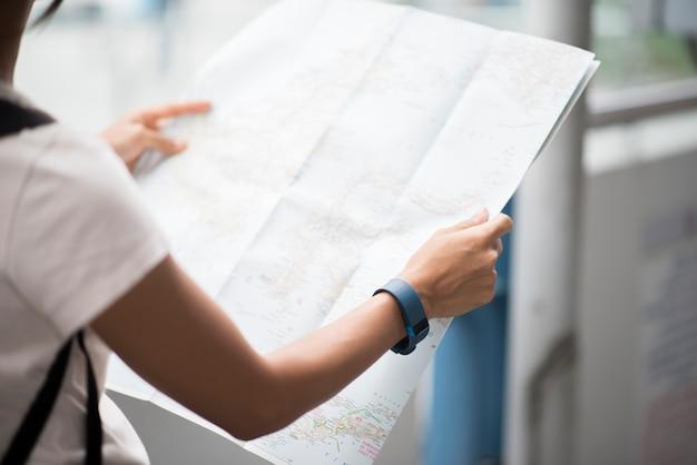Weiblicher tourist mit dem stadtplan, der bestimmungsort schaut