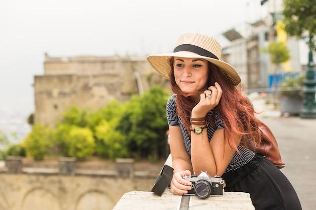Weiblicher tourist mit kamera auf dem balkon