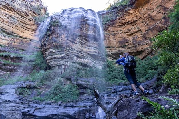 Weiblicher tourist mit rucksacktasche machen foto an wasserfall wentworth falls