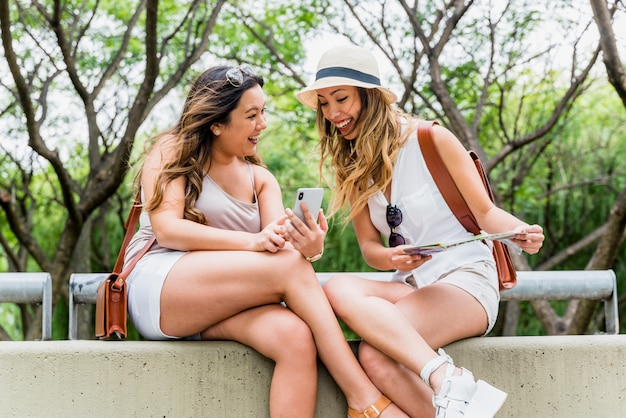 Weiblicher tourist zwei, der im park betrachtet handy sitzt