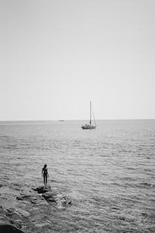 Weiblicher tragender bikini, der auf einem felsen durch das gewässer mit einem segelboot steht, das im meer schwimmt