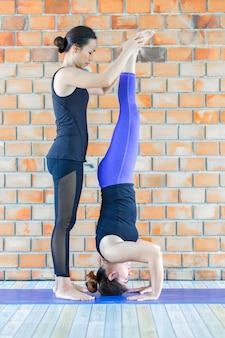 Weiblicher trainer der asiaten, der der jungen frau hilft, yoga zu tun.