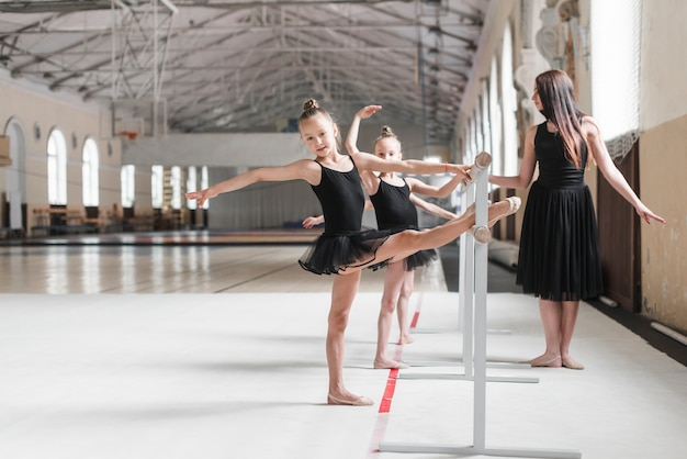 Weiblicher trainer, der ballerinamädchen ausdehnen ihr bein auf barre betrachtet