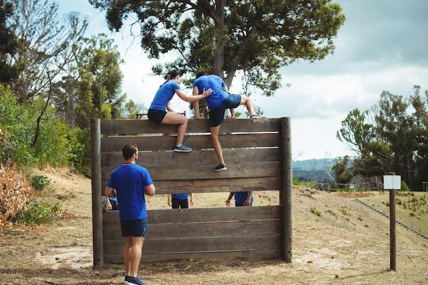 Weiblicher trainer, der fitten mann hilft, während des hindernislaufs über holzwand zu klettern