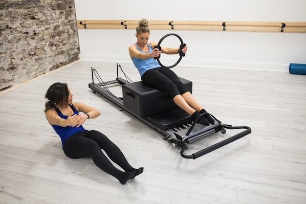 Weiblicher trainer, der frau beim trainieren mit pilates ring unterstützt