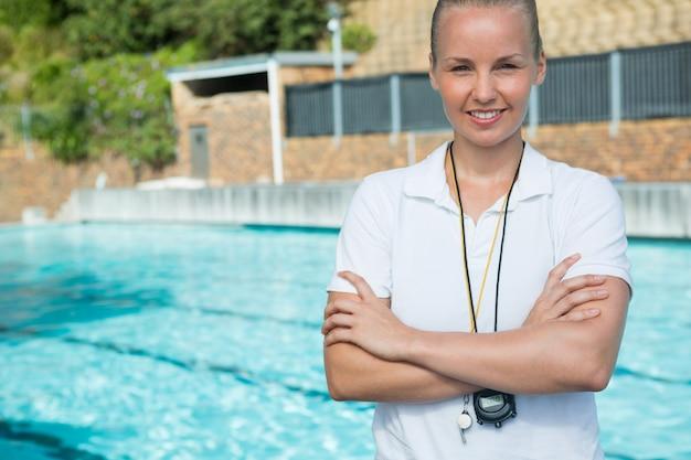 Weiblicher trainer, der mit verschränkten armen am pool steht
