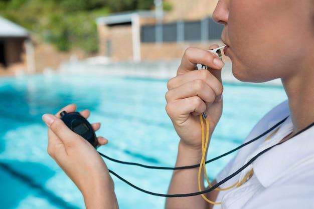 Weiblicher trainer, der pfeift und stoppuhr am pool betrachtet