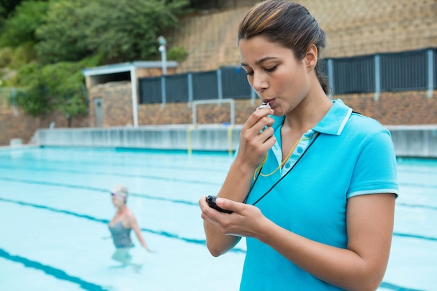 Weiblicher trainer, der pfeift und stoppuhr in der nähe des pools betrachtet