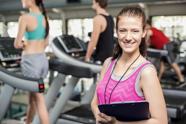Weiblicher trainer, der zur kamera an der turnhalle lächelt