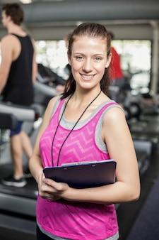 Weiblicher trainer, der zur kamera in der turnhalle lächelt
