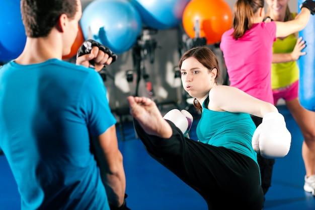 Weiblicher trittboxer mit trainer im sparring