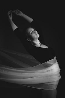 Weiblicher turner, der auf einem schwarzen hintergrund aufwirft