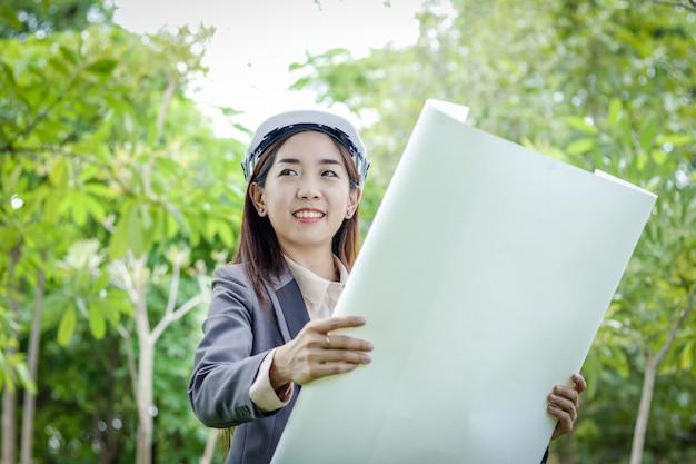 Weiblicher umweltingenieur, der einen anzug, einen weißen hut tragend trägt und stehen, halten einen papierplan