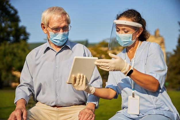 Weiblicher und alter mann, der den bildschirm des tablets betrachtet