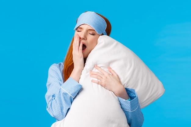 Weiblicher und glamouröser reizender rothaariger teenager, der gähnt und den mund öffnet, sich schläfrig und müde fühlt, ins bett geht, kissen umarmt, augen schließt, gute nacht hat, blaue wand steht