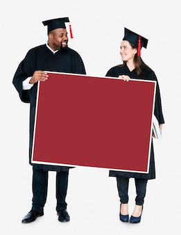 Weiblicher und männlicher absolvent, der einen kopienraum hält