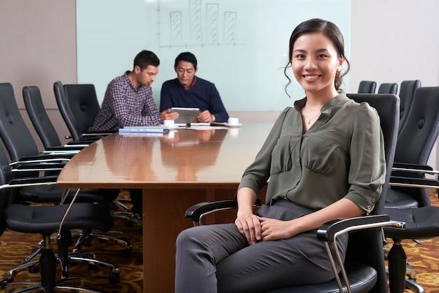 Weiblicher unternehmensleiter, der am schreibtisch mit ihren kollegen arbeiten an der digitalen auflage im hintergrund sitzt