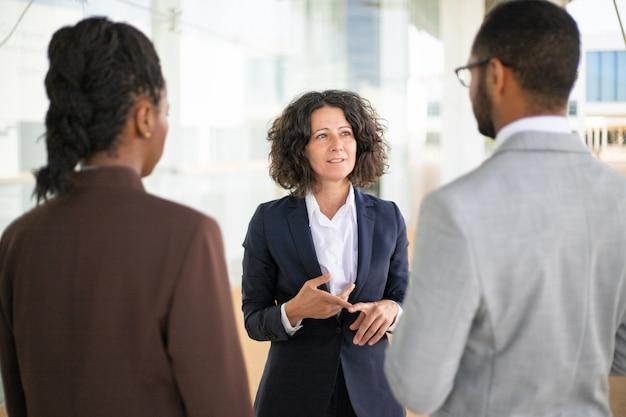 Weiblicher unternehmensleiter, der ihr team anweist