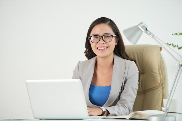 Weiblicher unternehmer, der sicher an der kamera sitzt am arbeitsschreibtisch lächelt