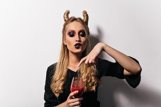 Weiblicher vampir, der blut aus weinglas trinkt. schöne blonde hexe, die poition in halloween genießt.