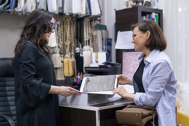Weiblicher verkäufer, der gewebe für proben von teppichen zeigt