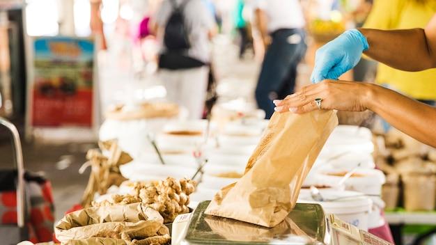 Weiblicher verkäufer, der lebensmittel in der braunen papiertüte am lebensmittelgeschäftmarktstall wiegt