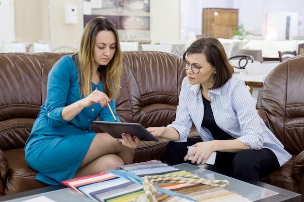 Weiblicher verkäufer und käufer im gewebespeicher