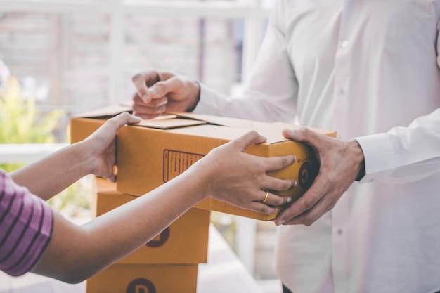 Weiblicher verkäuferhauptgeschäftseigentümer, der paket zum kunden behandelt